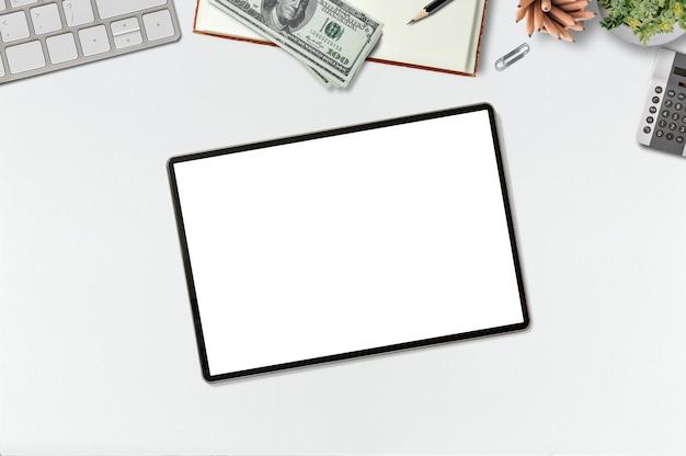 Mesa de escritório de maquete com tablet de tela em branco, laptop, dinheiro e suprimentos.
