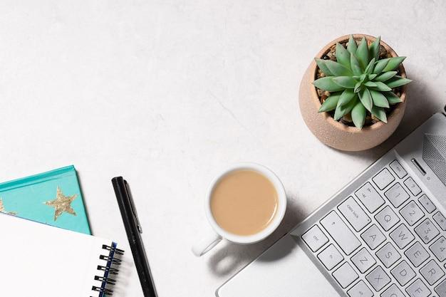 Mesa de escritório de mármore branco com laptop, notebook, xícara de café e uma flor suculenta em uma panela