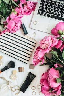 Mesa de escritório de moda feminina com flores de peônia, laptop, cosméticos e acessórios em fundo branco, vista de cima plana