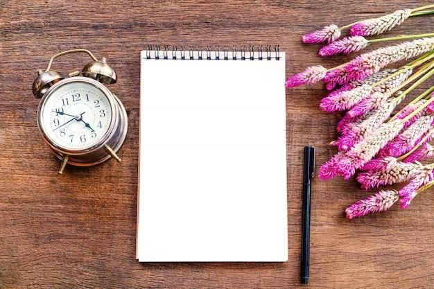 Mesa de escritório de negócios com bloco de notas, flores na mesa de madeira