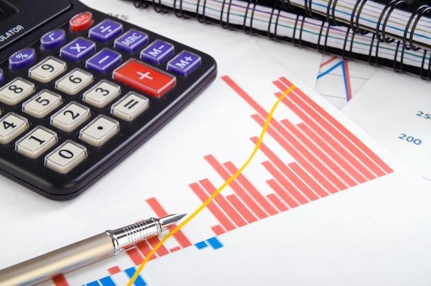 Mesa de escritório de negócios com diagrama, caneta e calculadora