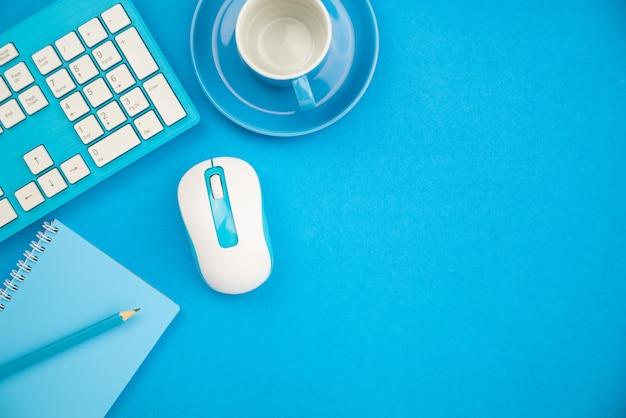 Mesa de escritório de negócios com objetos de negócios de teclado, mouse, lápis, nota de papel e xícara de café sobre fundo azul