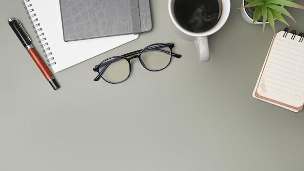 Mesa de escritório de vista superior com notebooks, copos, xícara de café e planta.