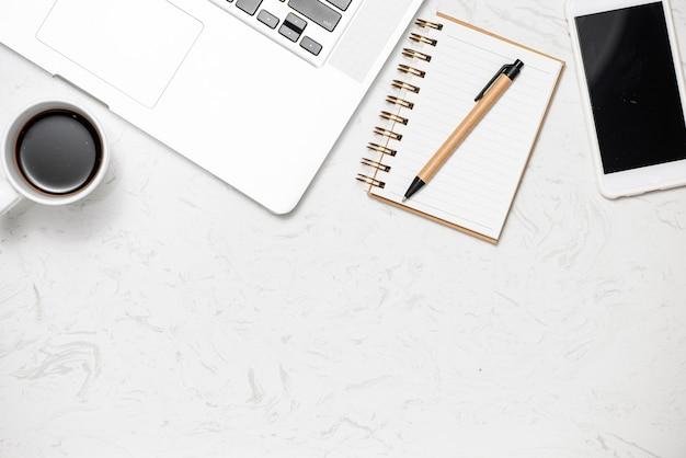 Mesa de escritório de vista superior com teclado, notebooks e xícara de café em fundo de mármore.