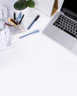 Mesa de escritório de vista superior e espaço de trabalho com espaço em branco sobre fundo branco.