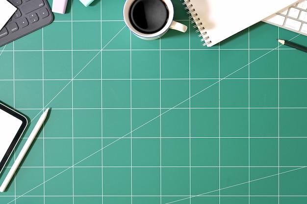 Mesa de escritório designer e tablet na esteira de corte verde