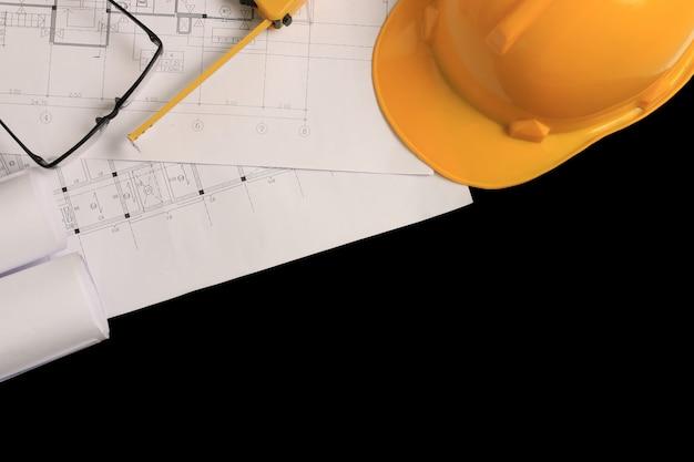 Mesa de escritório do arquiteto com desenhos de construção e capacete