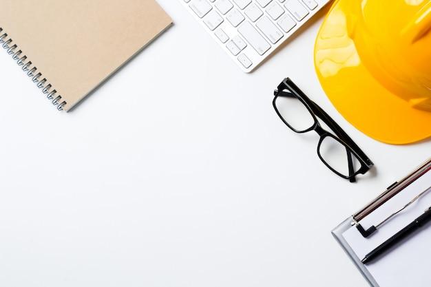Mesa de escritório do arquiteto com ferramentas, capacete, computador, óculos e notebook.