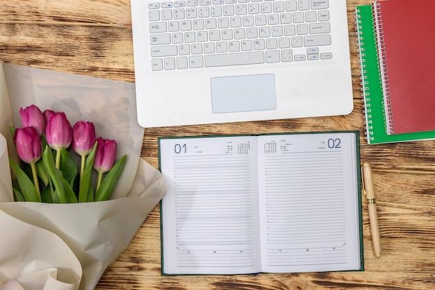 Mesa de escritório e buquê de tulipas vista superior