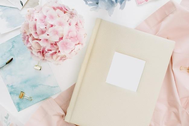 Mesa de escritório em casa com álbum de fotos do casamento da família, buquê de flores de hortênsia colorida em tons pastéis, cobertor cor de pêssego, decoração na superfície branca