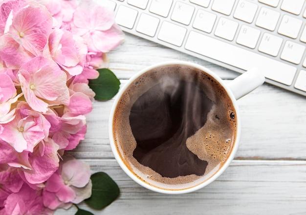 Mesa de escritório em casa com buquê de flores de hortênsia rosa, xícara de café e teclado