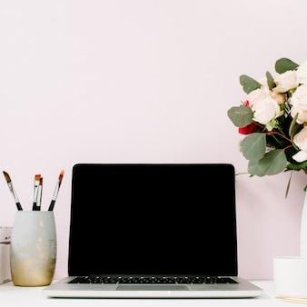 Mesa de escritório em casa com laptop de tela em branco, lindas rosas e buquê de eucalipto, caixão vintage branco na frente de rosa pastel claro
