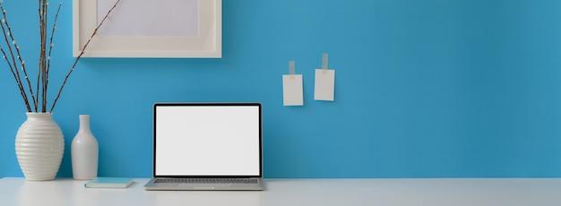 Mesa de escritório em casa criativa com laptop, notebook, decorações e espaço de cópia