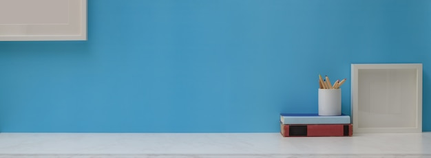 Mesa de escritório em casa criativa com quadros, livros, artigos de papelaria e cópia espaço