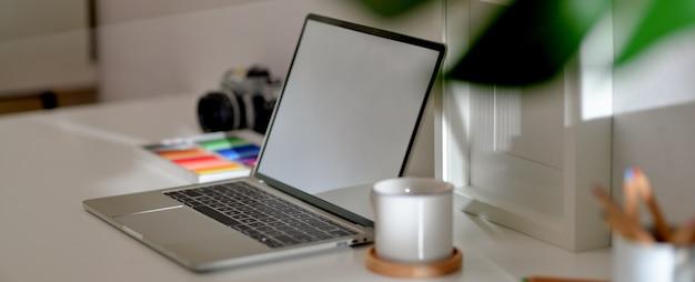 Mesa de escritório em casa de design com laptop, copo, câmera, suprimentos e decorações