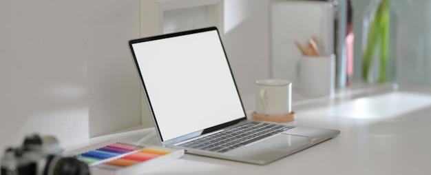 Mesa de escritório em casa de design com laptop, copo, suprimentos e decorações