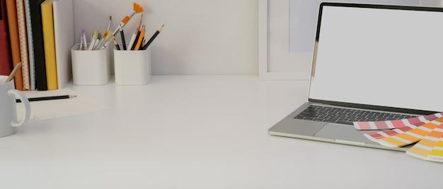 Mesa de escritório em casa de design com laptop, ferramentas de pintura, suprimentos e cópia espaço