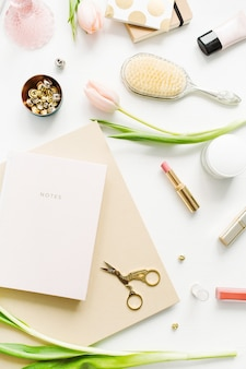 Mesa de escritório em casa de mulheres com flores de tulipa rosa, caderno, acessórios e cosméticos em fundo branco. flatlay, vista superior