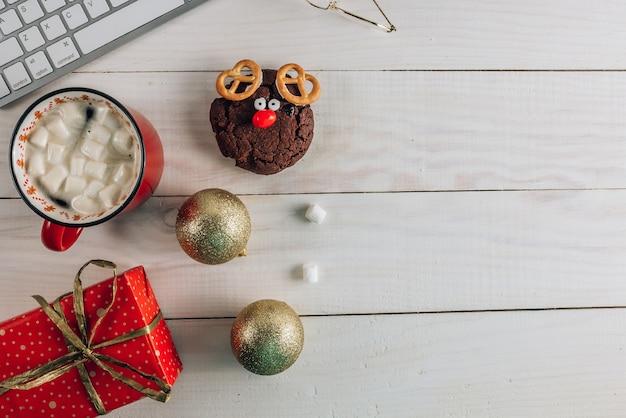 Mesa de escritório em casa de natal com computador, presente, biscoitos, café e decorações de ouro de natal.