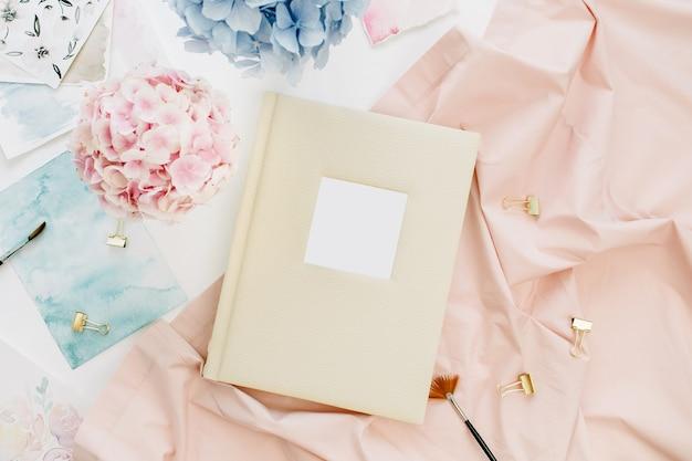 Mesa de escritório em casa do artista com álbum de fotos de casamento de família, buquê de flores de hortênsia colorida em tons pastel, cobertor cor de pêssego, decoração em superfície branca