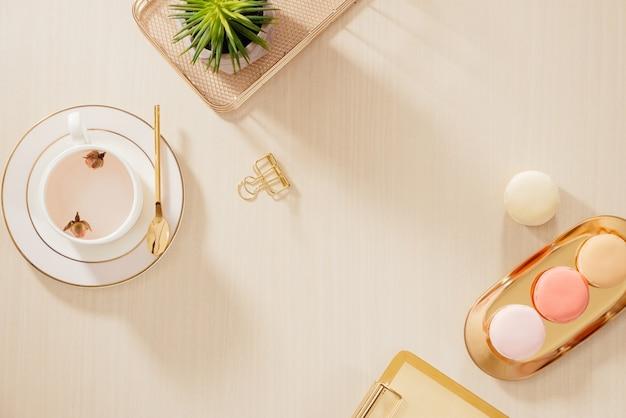 Mesa de escritório em casa estilizada ouro moderna com pasta, macaroons, caneca de café em fundo bege. conceito de estilo de vida com vista de cima.