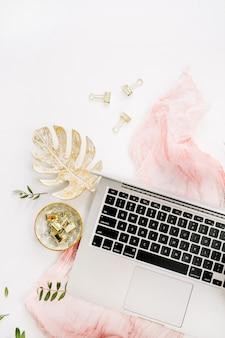 Mesa de escritório em casa feminina com laptop, buquê de flores de hortênsia rosa, cobertor pastel, placa de folha monstera e acessórios na superfície branca