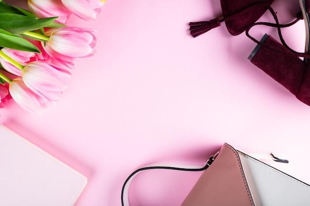 Mesa de escritório em casa feminina. espaço de trabalho com caderno, flores de tulipa rosa e acessórios. camada plana, vista superior. fundo do blog de moda. mulheres categoricamente. conceito de moda.