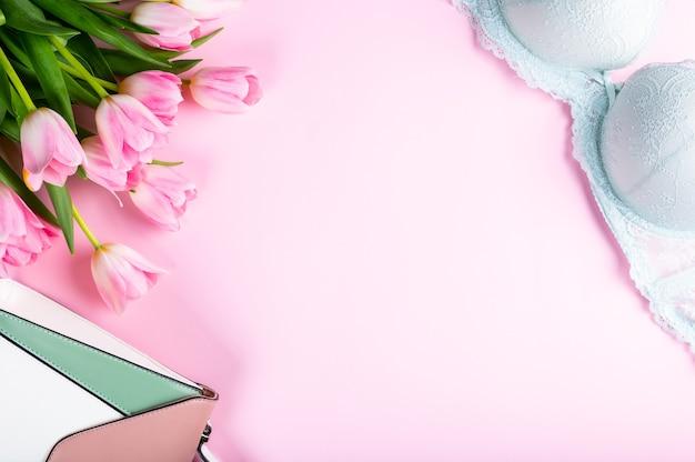 Mesa de escritório em casa feminina. espaço de trabalho com caderno, flores de tulipa rosa e acessórios. camada plana, vista superior. fundo do blog de moda. mulheres categoricamente. flatlay do dia da mulher.