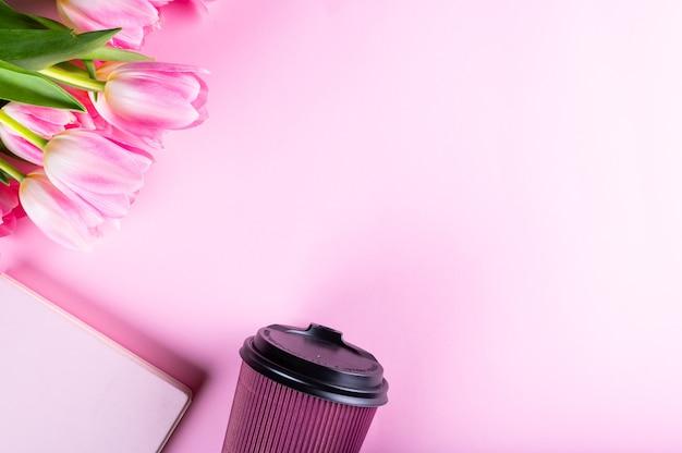 Mesa de escritório em casa feminina. espaço de trabalho com caderno, flores de tulipa rosa e acessórios. camada plana, vista superior. fundo do blog de moda. mulheres categoricamente.