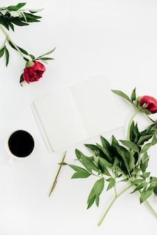 Mesa de escritório em casa mínima com caderno, café e flores de peônia na superfície branca