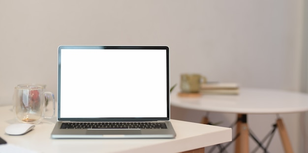 Mesa de escritório em casa mínima com laptop de tela em branco Foto Premium