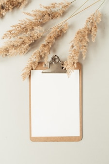 Mesa de escritório em casa minimalista plana leiga com prancheta de folha em branco com espaço de cópia para texto, ramo de juncos, caixão em fundo neutro. modelo de trabalho, negócios, educação de vista superior.