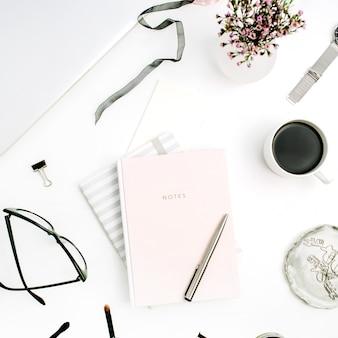 Mesa de escritório em casa moderna feminina com caderno rosa pastel, óculos, xícara de café, flores silvestres. camada plana, vista superior