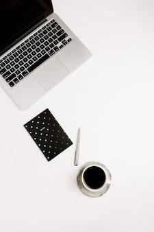 Mesa de escritório em casa plana e moderna com laptop, notebook e café branco