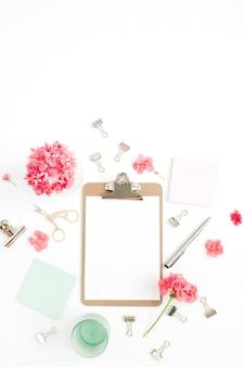 Mesa de escritório em casa plana leigos. área de transferência com espaço de cópia para texto, flores vermelhas, acessórios, diário de hortelã em branco