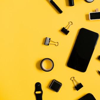 Mesa de escritório em casa plana leigos. espaço de trabalho com laptop, acessórios masculinos: diário, relógio, celular em amarelo