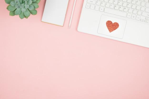 Mesa de escritório em casa plana leigos. espaço de trabalho de mulheres com laptop, caderno, caneta na superfície rosa. vista superior da superfície feminina.