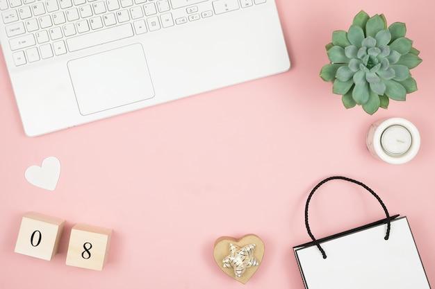 Mesa de escritório em casa plana leigos. espaço de trabalho de mulheres com laptop e dados na superfície rosa. conceito de dia mundial das mulheres dia 8 de março