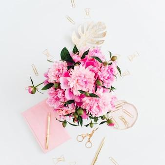 Mesa de escritório em casa plana leigos. espaço de trabalho feminino com buquê de peônias rosa, acessórios dourados, diário rosa em branco