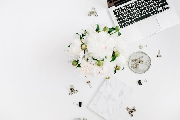 Mesa de escritório em casa plana leigos. espaço de trabalho feminino com laptop, buquê de flores de peônia branca, acessórios, diário de mármore em branco