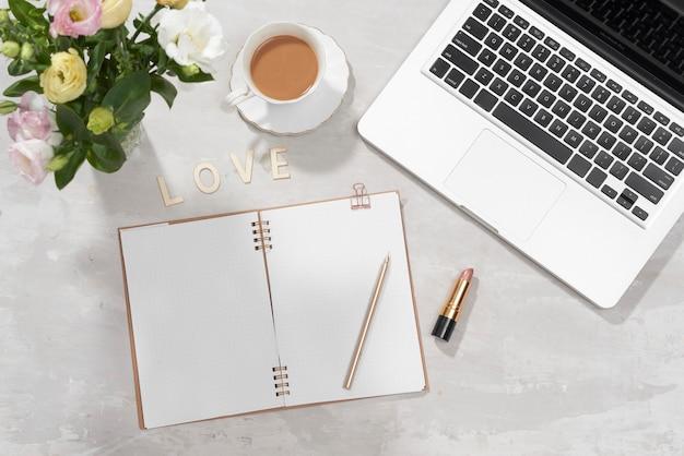Mesa de escritório em casa plana leigos. espaço de trabalho feminino com laptop, buquê de lisianthus rosa, batom, diário e carta de amor em branco