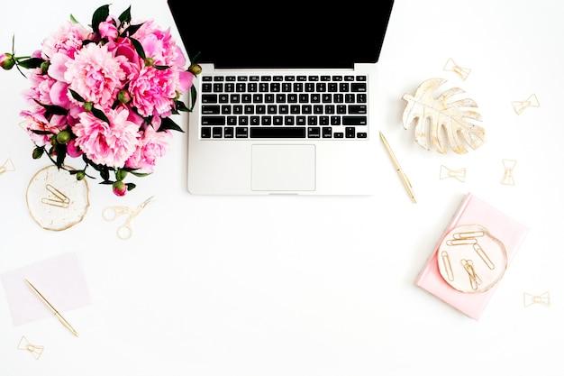 Mesa de escritório em casa plana leigos. espaço de trabalho feminino com laptop, buquê de peônias rosa, acessórios dourados, diário rosa em branco