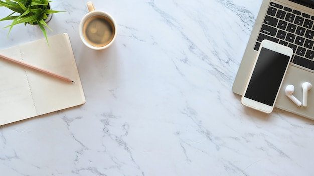Mesa de escritório em mármore com laptop, smartphone de tela em branco preto, fone de ouvido sem fio, lápis, notas e colocação de vasos de plantas.