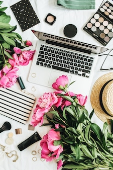 Mesa de escritório feminina de moda plana com laptop, flores de peônia rosa, cosméticos, acessórios