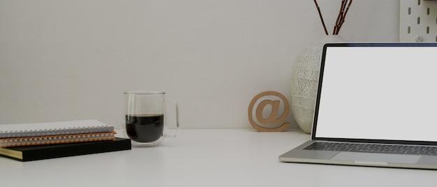 Mesa de escritório moderna com espaço de cópia, laptop, agendar livros, xícara de café e decorações