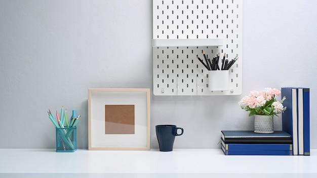 Mesa de escritório moderna com moldura vazia, livros, artigos de papelaria e xícara de café na mesa branca