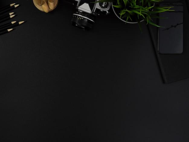 Mesa de escritório moderna escura com artigos de papelaria, smartphone, câmera, decorações e espaço de cópia