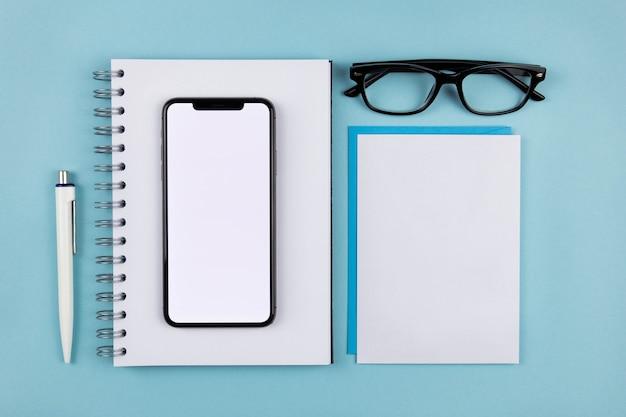 Mesa de escritório moderna plana com maquete de tela do smartphone, bloco de notas de papel em espiral, envelopes brancos em branco e óculos de leitura na superfície azul