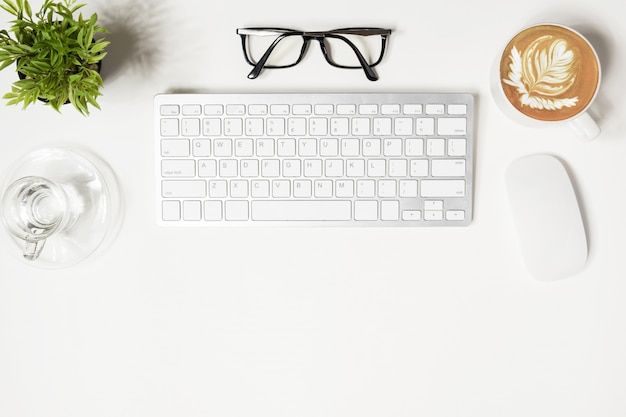 Mesa de escritório moderno branco com gadgets de computador e suprimentos.