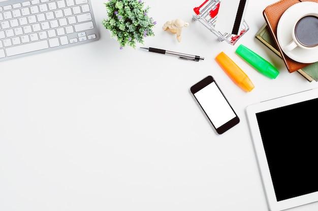 Mesa de escritório moderno branco com teclado, caneta, notebook, smartphone, tablet, cartão de crédito e copa